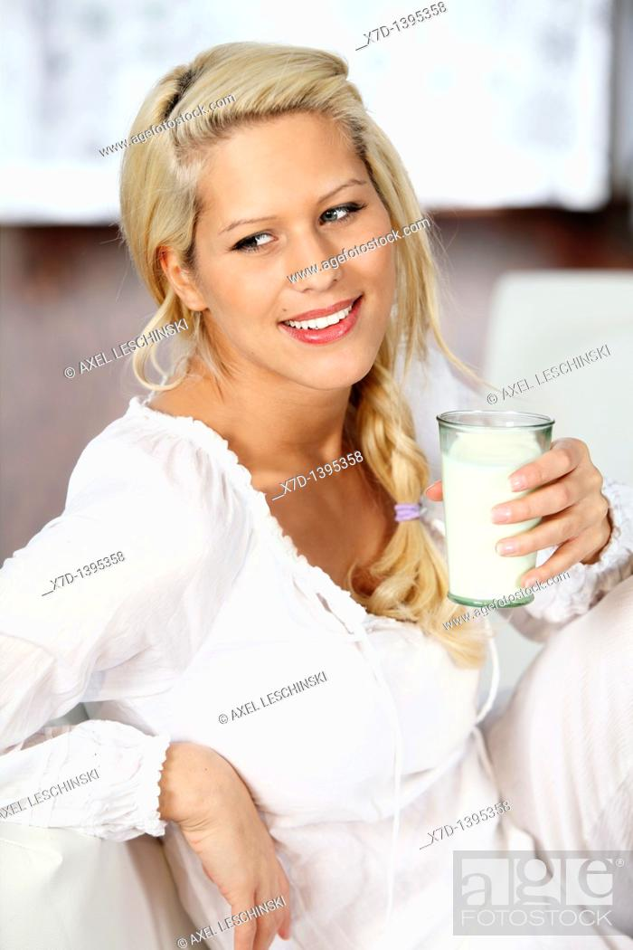 Stock Photo: blond woman relaxing on sofa drinking a glass of milk.