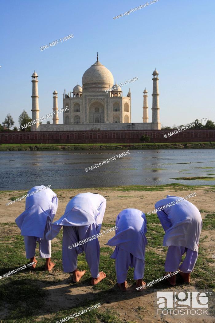 Stock Photo: Young muslim boys performing religious prayer Namaz in front of Taj Mahal Seventh Wonders of World on south bank of Yamuna river , Agra , Uttar Pradesh.