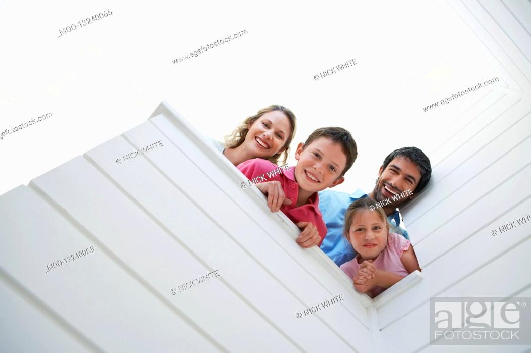 Stock Photo: Family peering over white wall view from below.