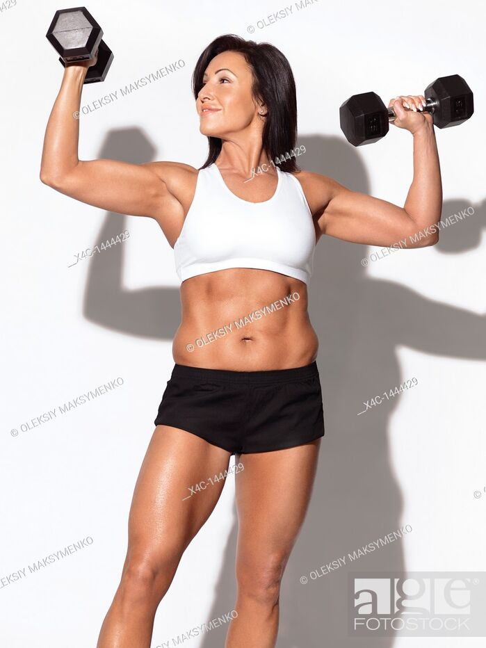 Stock Photo: Portrait of a smiling fitness woman with dumbbells in her forties  Isolated on white background.