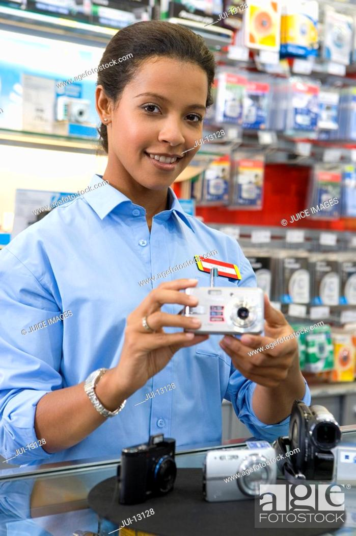 Stock Photo: Young saleswoman with camera, smiling, portrait, low angle view.