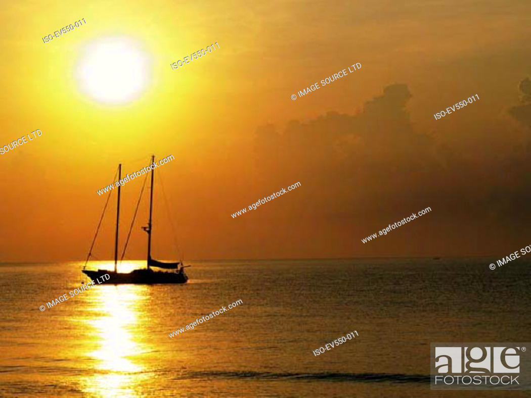 Stock Photo: Sailing boat in sunset.