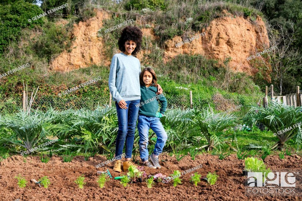 Stock Photo: Mother and son standing in vegetable garden with lettuce seedlings.