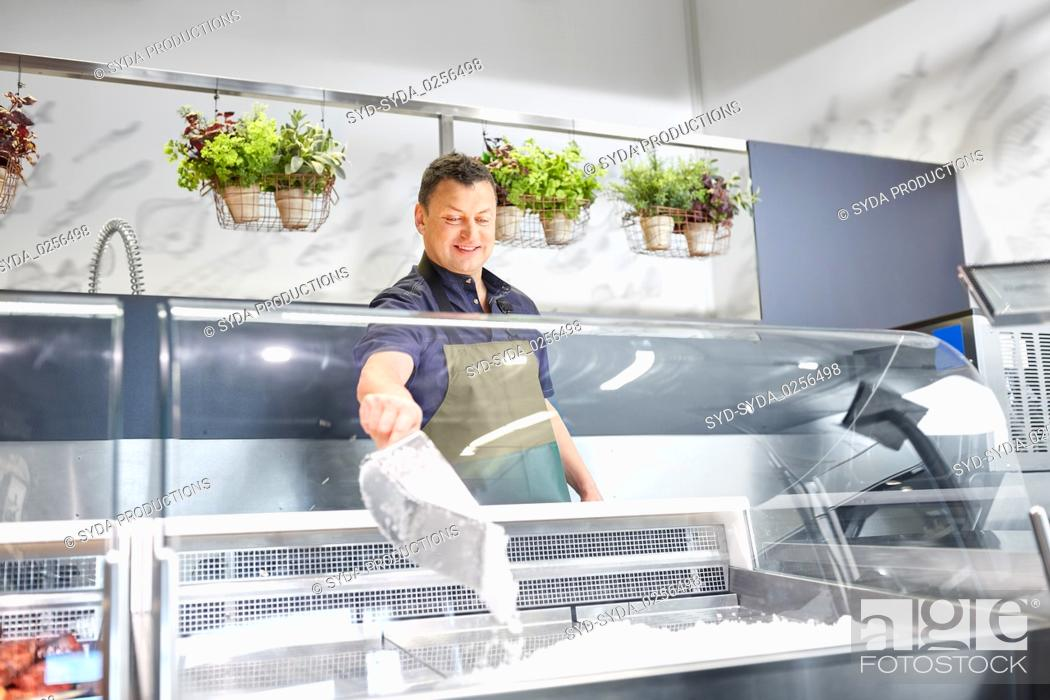 Photo de stock: male seller adding ice to fridge at grocery store.