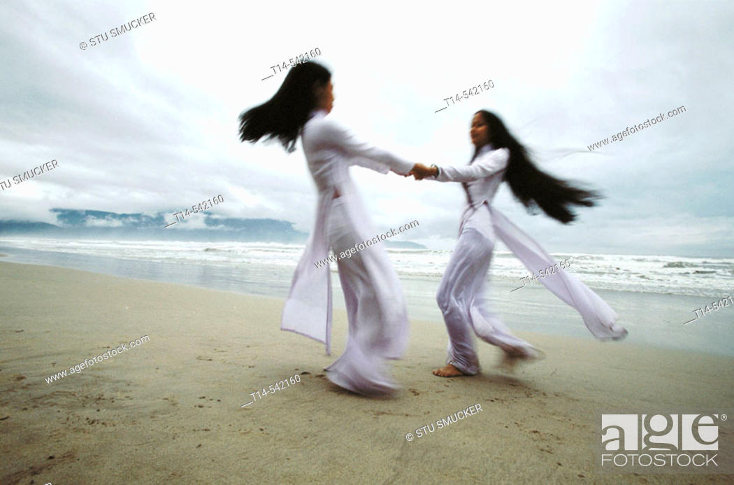 Stock Photo: Two schoolgirls in national dress dance on the beach as a tropical storm gathers off Danang's coast. Quang Nam province. Vietnam.