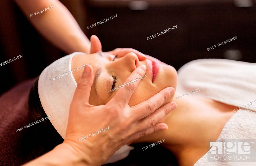 Stock Photo: people, beauty, lifestyle and relaxation concept - beautiful young woman lying with closed eyes and having face and head massage at spa.