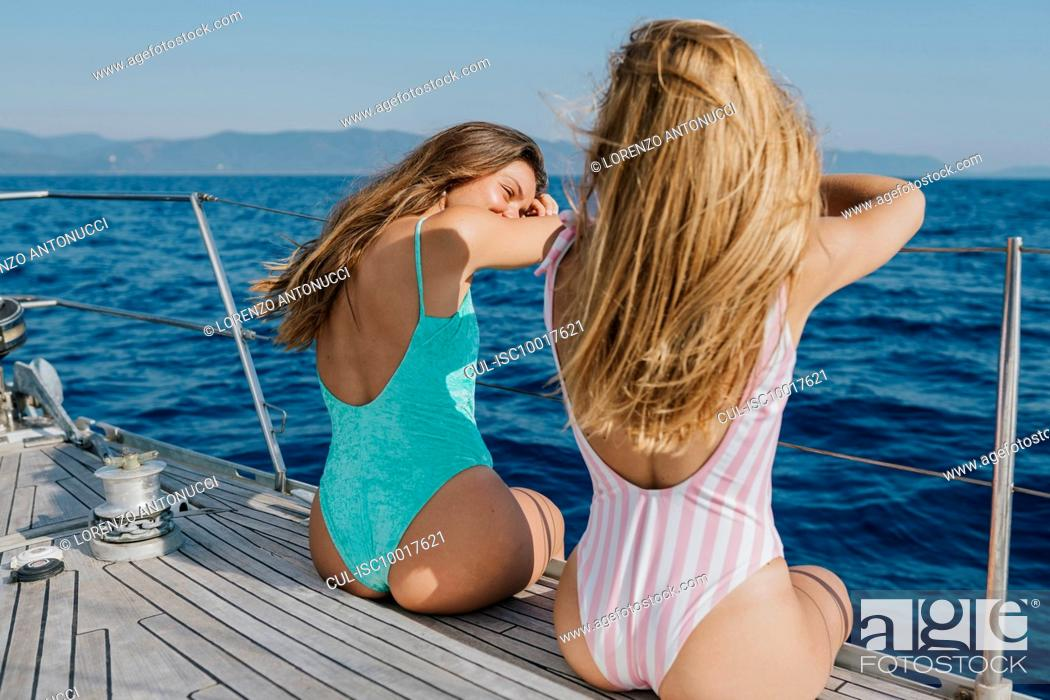 Imagen: Friends relaxing on deck edge of sailboat, Italy.