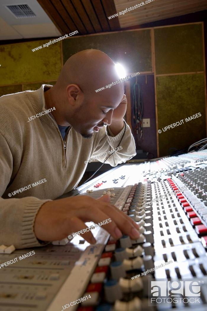 Stock Photo: Music producer adjusting sound equipment.