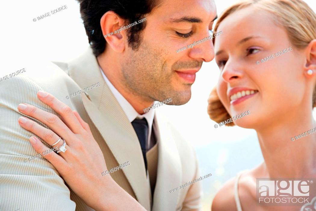 Stock Photo: Bride wearing wedding ring with hand on groom's shoulder.