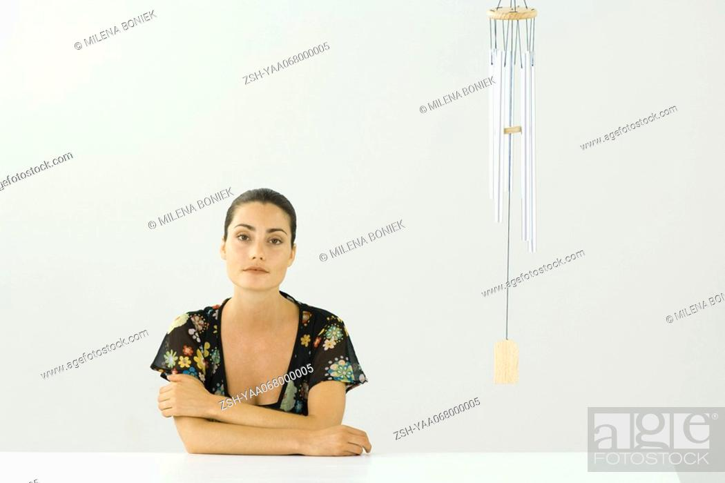 Stock Photo: Woman sitting beside wind chime, arms folded, smiling at camera.