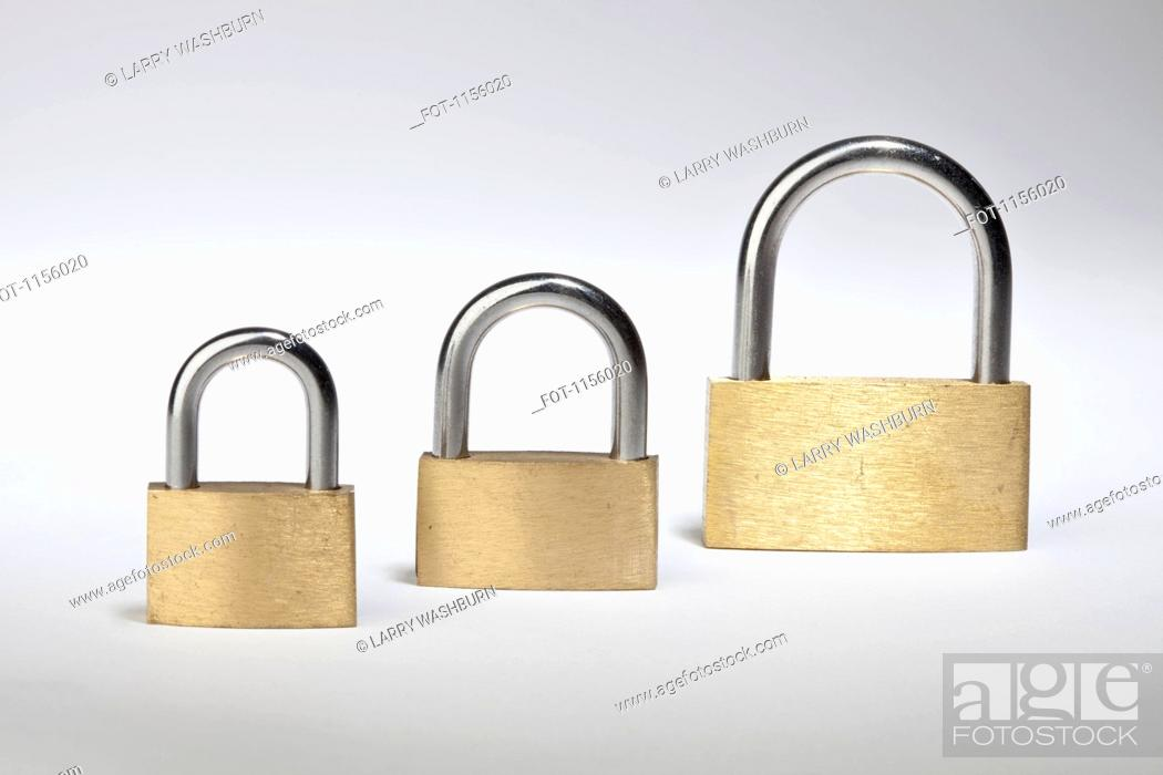 Stock Photo: Three different sized padlocks in a row.