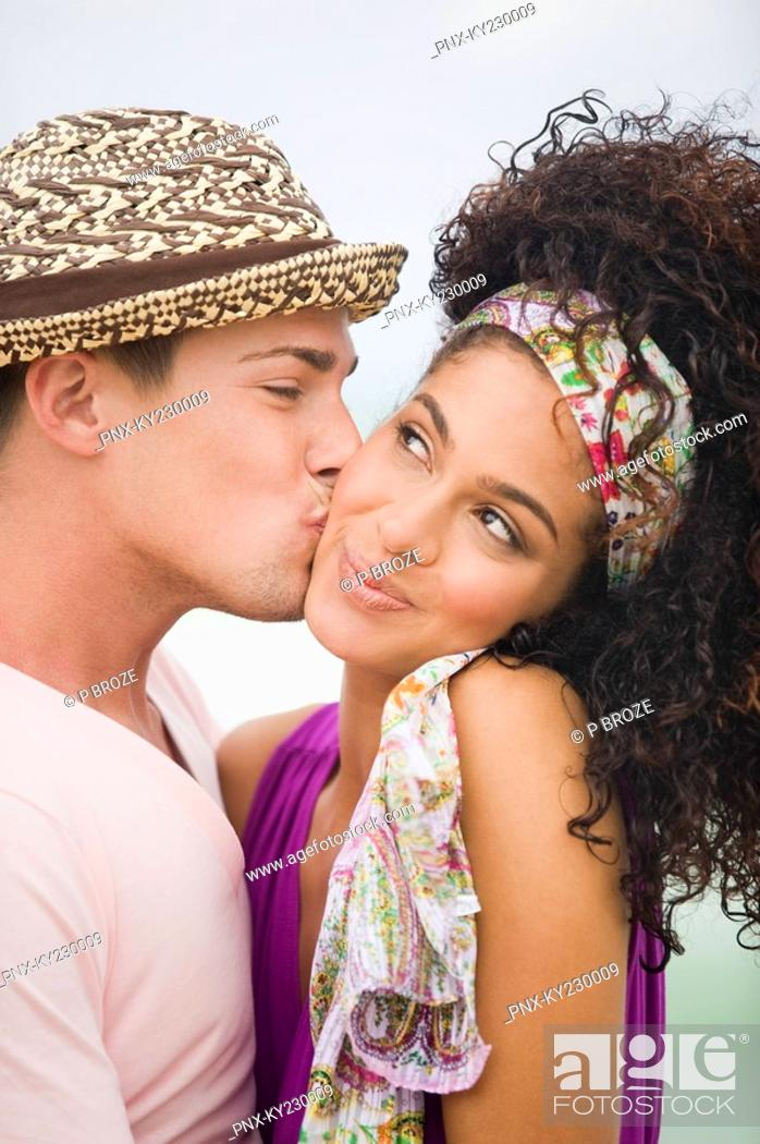 Stock Photo: Man kissing a woman on cheek.