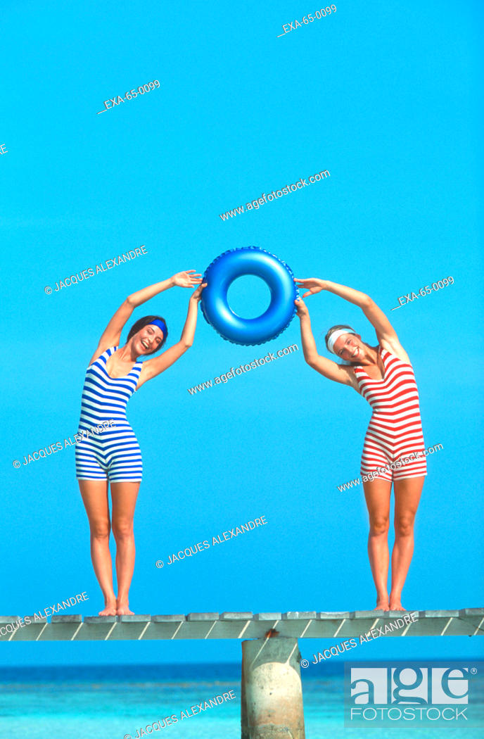 f77ca03f3d1 Stock Photo - Two women in old fashioned bathing suits holding inner tube  at beach