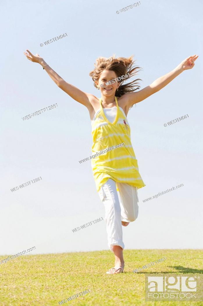Stock Photo: Spain, Mallorca, Girl 10-11 running across meadow.
