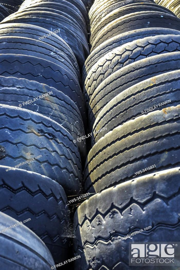 Stock Photo: Used and worn lorry tyres stored at a garage, Scotland, UK.