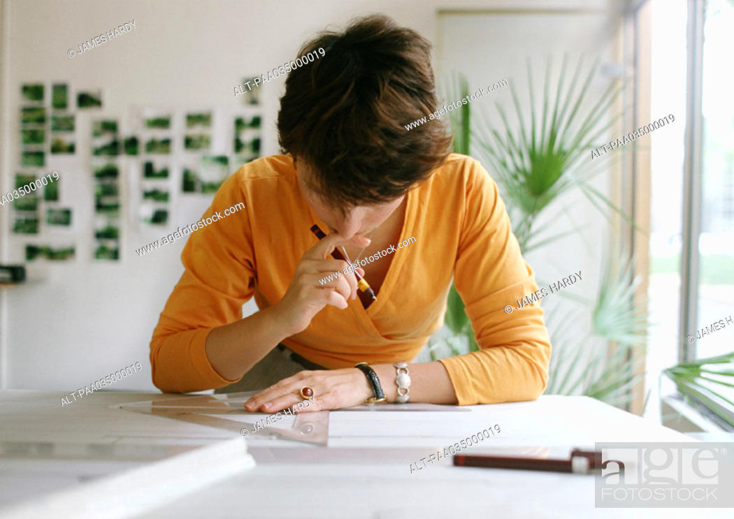 Stock Photo: Woman bending over table, holding set square and pen.