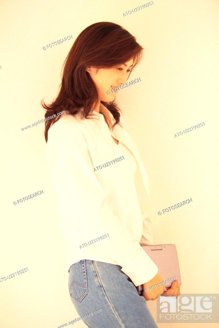 Imagen: Image of a Young Adult Woman Holding a Laptop, Standing In Front of a White Wall, Side View.
