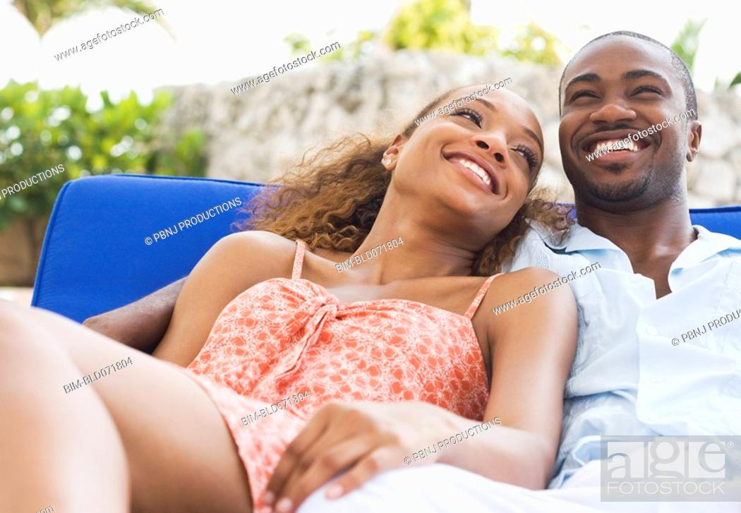 Stock Photo: African American couple laying on lounge chair.