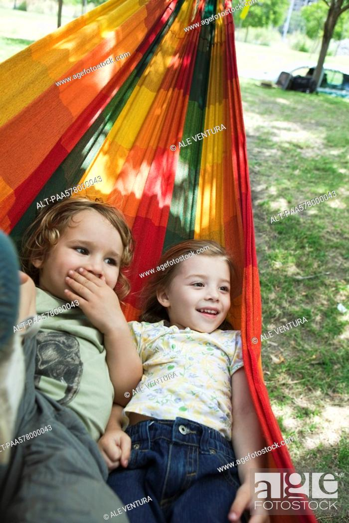 Stock Photo: Young brother and sister lying in hammock together.