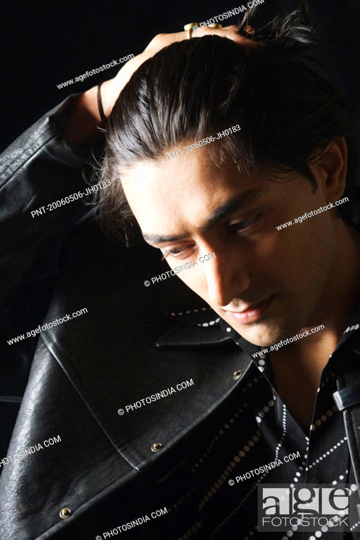 Stock Photo: Close-up of a young man with his hand in his hair.
