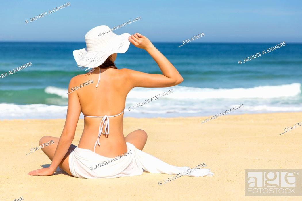 Imagen: woman with sun hut sits in front of the sea.
