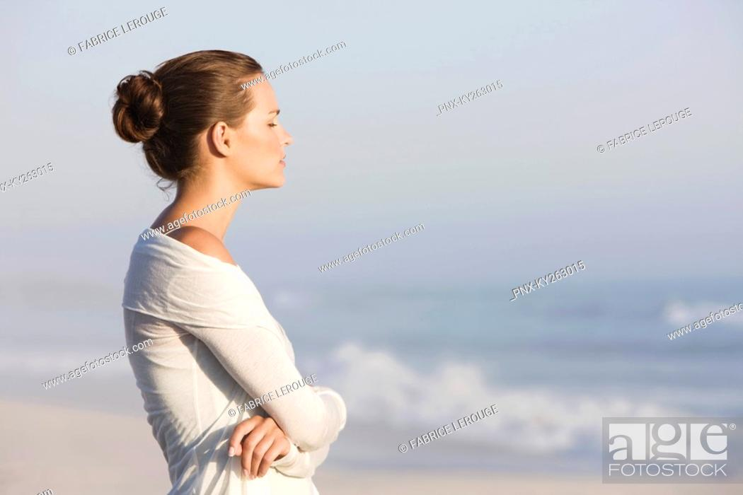 Stock Photo: Woman standing on the beach and thinking.