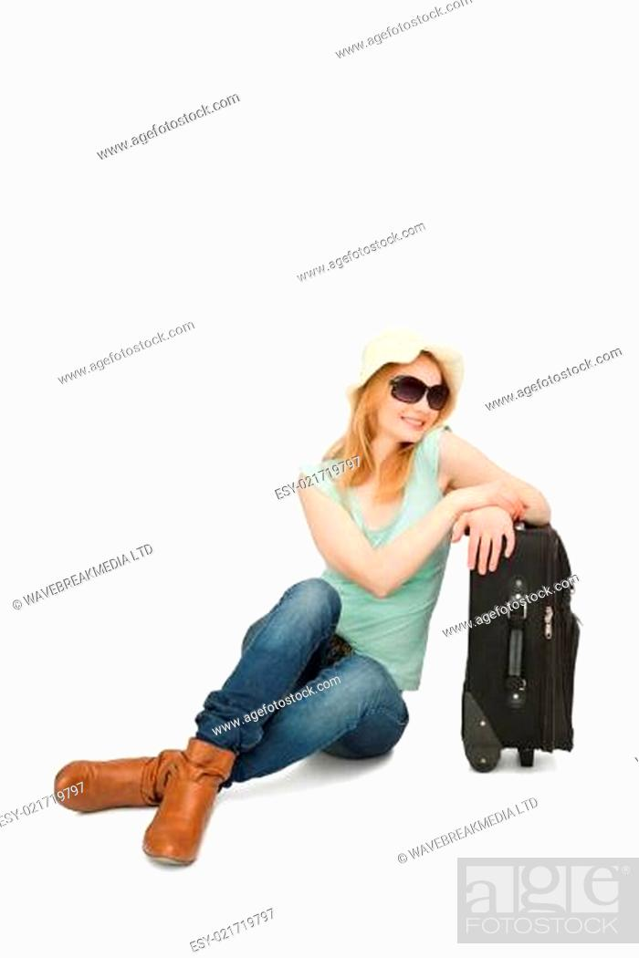 Stock Photo: Woman smiling while sitting near a suitcase.
