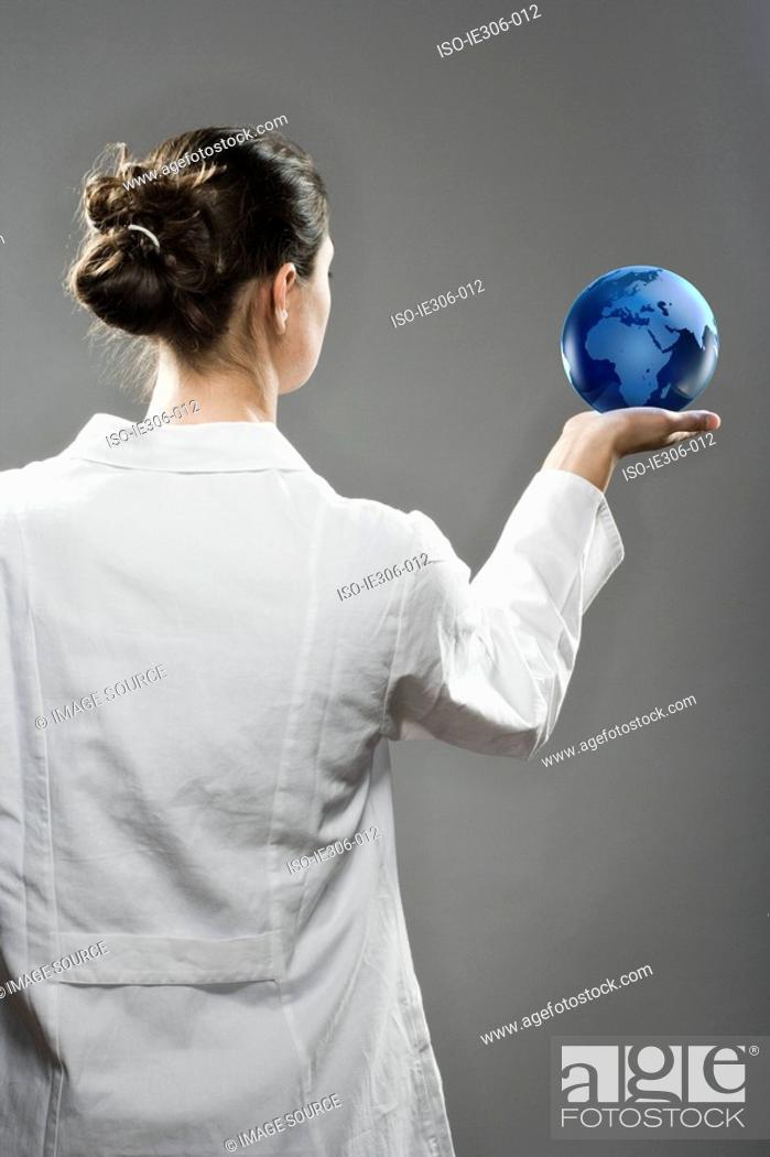 Stock Photo: Female scientist holding a globe.