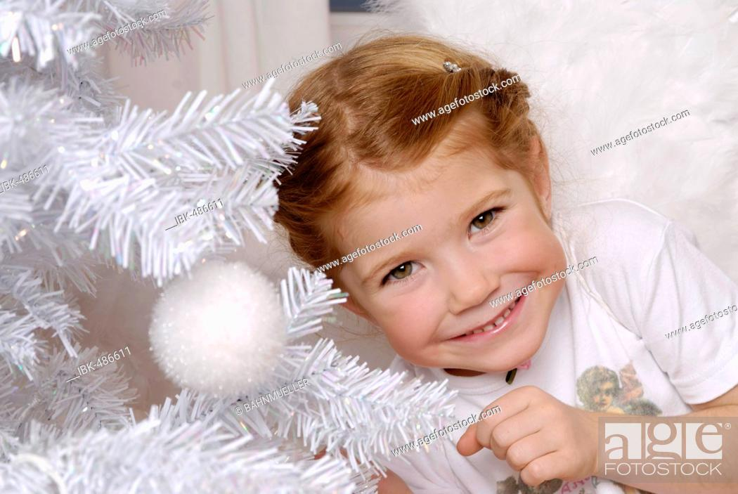 Stock Photo: Child decorates a white christmas tree.