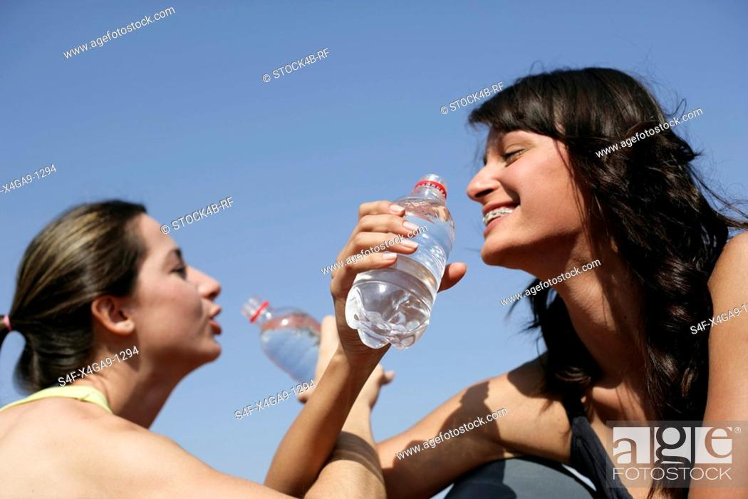 Stock Photo: Two women drinking to close friendship with each other.