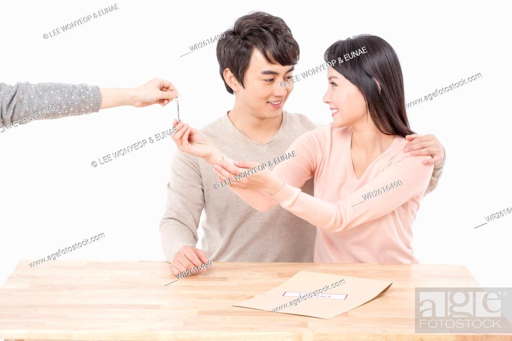 Stock Photo: Young newlyweds getting a key.