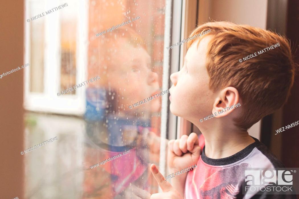 Imagen: Boy looking at the rain on windowpane.