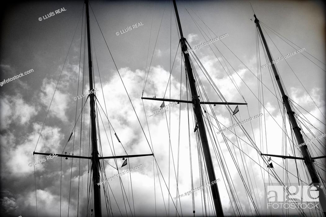 Stock Photo: Three wooden masts of a classic sailboats with a background of sky with clouds.