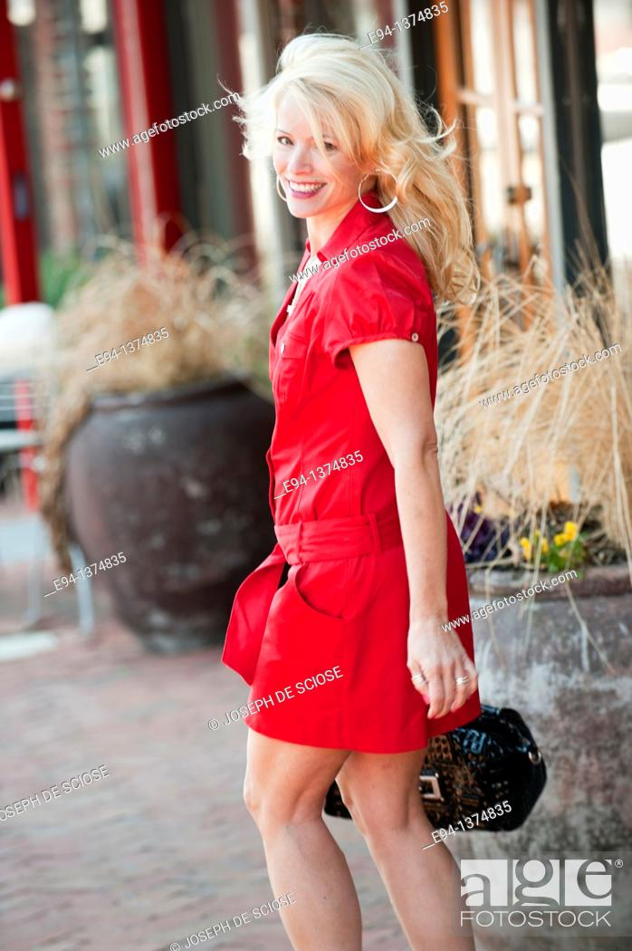 Stock Photo: A 44 year old blond woman wearing a red dress walking on a side walk in an urban setting.