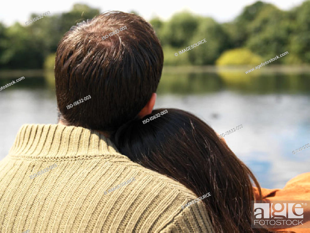 Stock Photo: Couple sitting near lake.