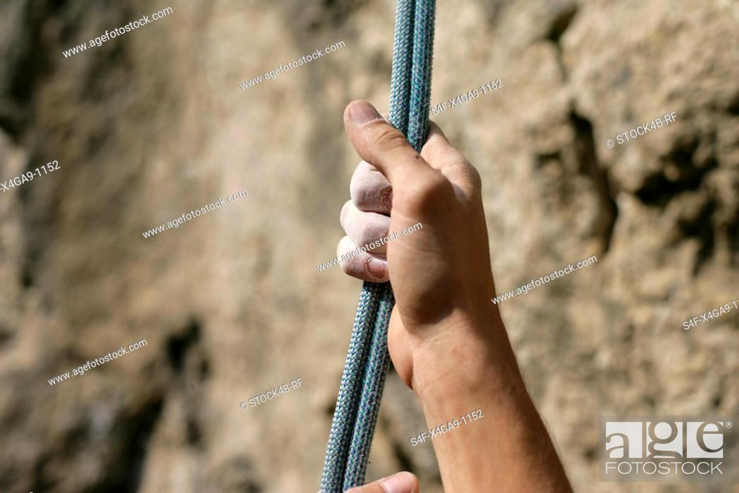 Stock Photo: Dirty male hand touching a rope in front of a rocky wall, close-up, selective focus.
