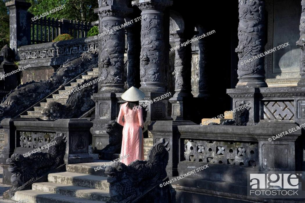 Stock Photo: Girl in Ao Dai traditional Vietnamese long dress and conical hat at Tomb of King Khai Dinh, Hue, Vietnam.