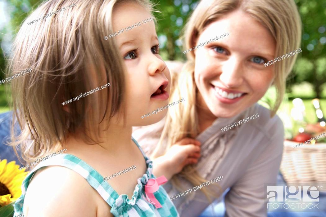 Stock Photo: Germany, Cologne, Mother and daughter at picnic, smiling.