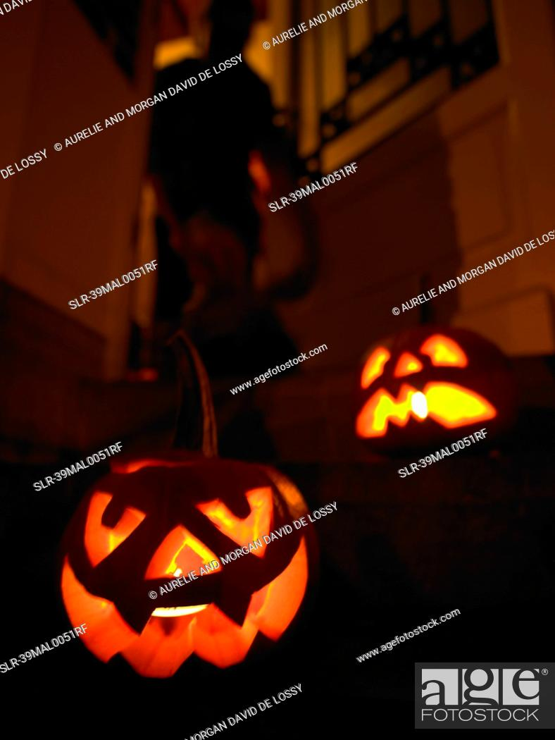 Stock Photo: Glowing jack olanterns on front steps.