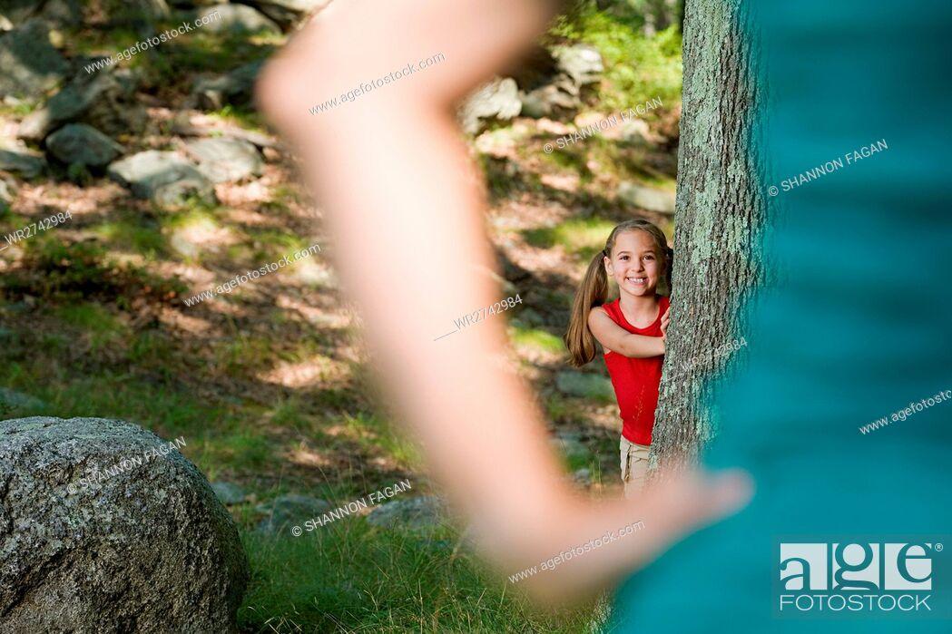 Stock Photo: Girl hiding behind a tree.