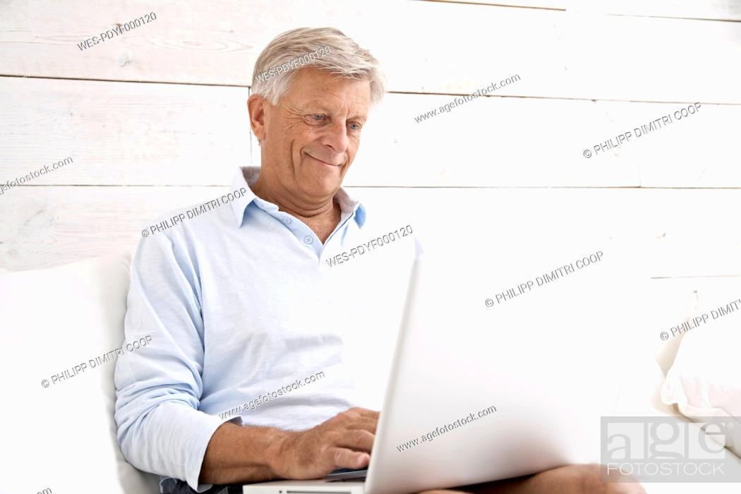 Stock Photo: Spain, Senior man checking emails on laptop, smiling.
