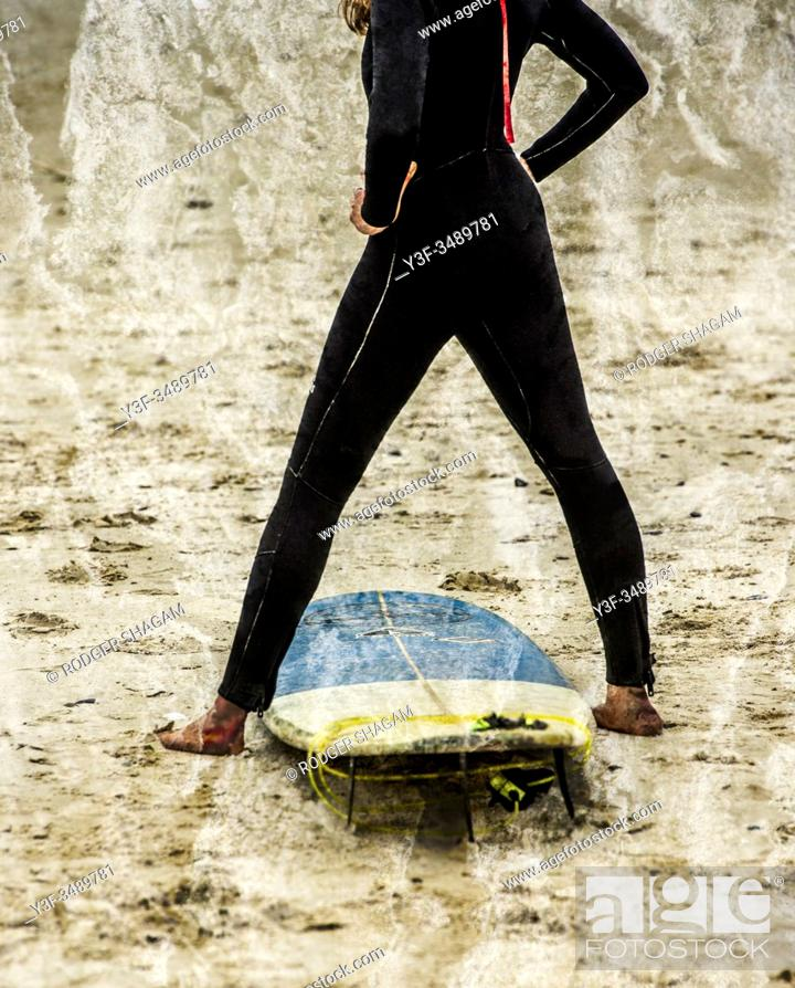 Stock Photo: Young woman doing stretches on the beach before taking to the water to start surfing.