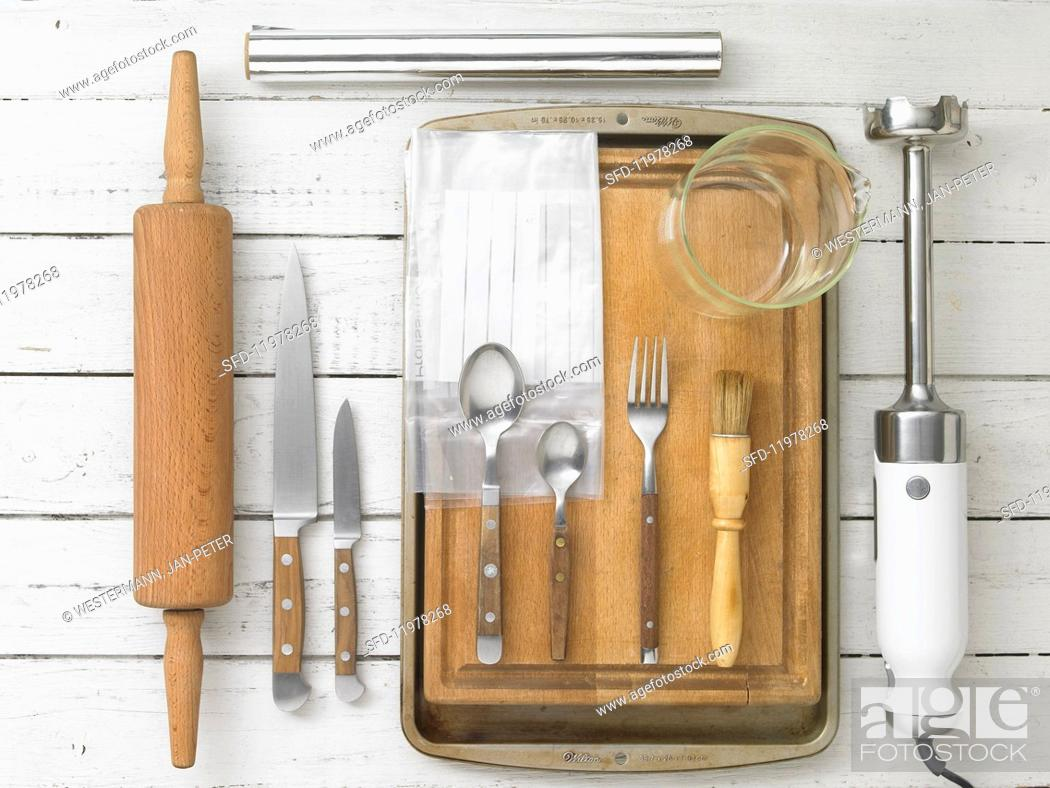 Stock Photo: Kitchen utensils: a rolling pin, knives, cutlery, a pastry brush and a hand blender.
