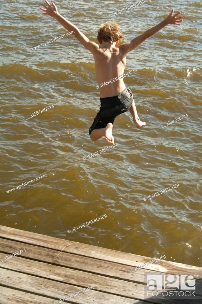 Stock Photo: Boy jumping from boat dock into the Albemarle Sound.
