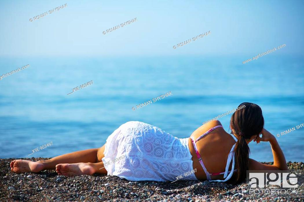 Stock Photo: A beautiful woman relaxing on a beach.