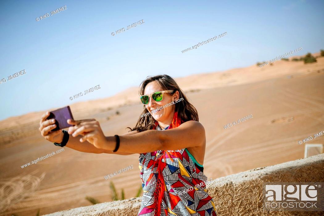 Stock Photo: Morocco, Merzouga, smiling torist taking selfie with smartphone.