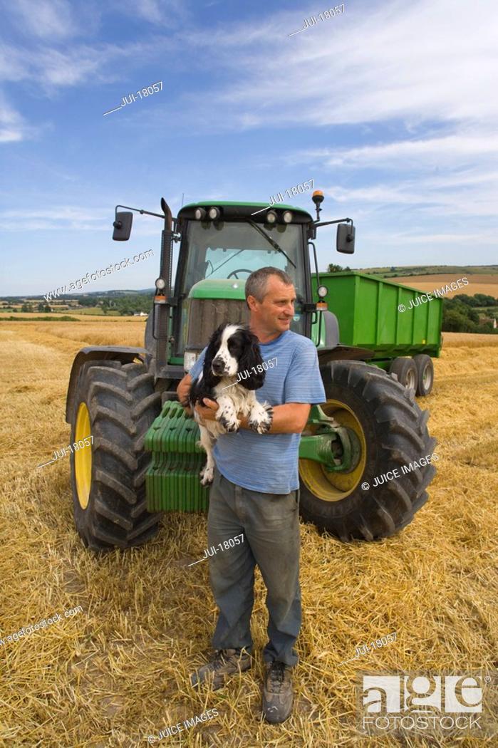 Stock Photo: Farmer holding dog near tractor.