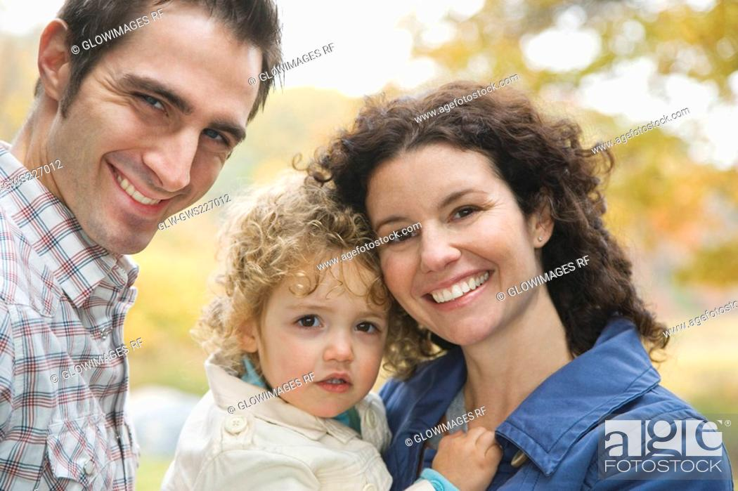 Stock Photo: Portrait of a couple smiling with their daughter.