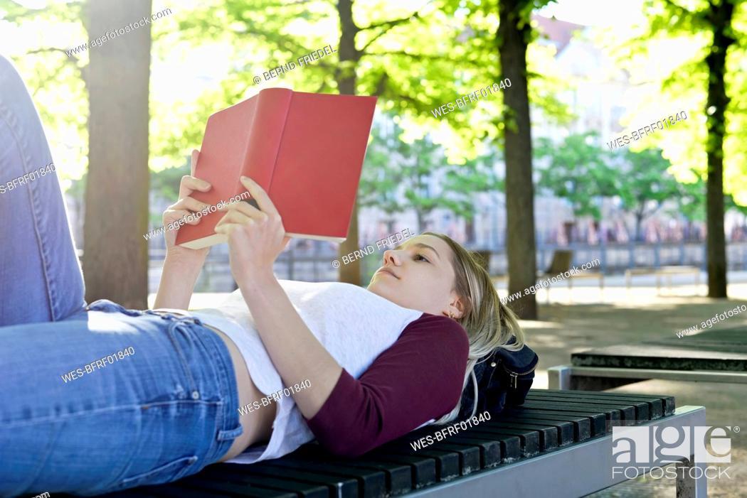 Photo de stock: Young woman reading a book on bench.