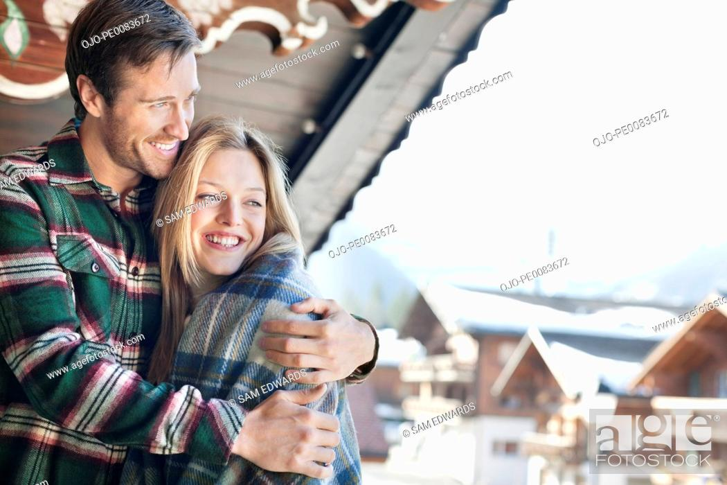 Stock Photo: Smiling couple hugging on cabin porch.